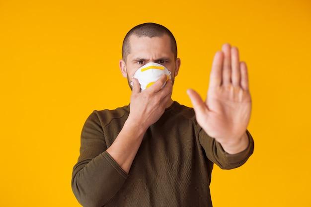 Homem caucasiano gesticulando a placa de pare enquanto segura uma máscara protetora no rosto, posando em uma parede amarela