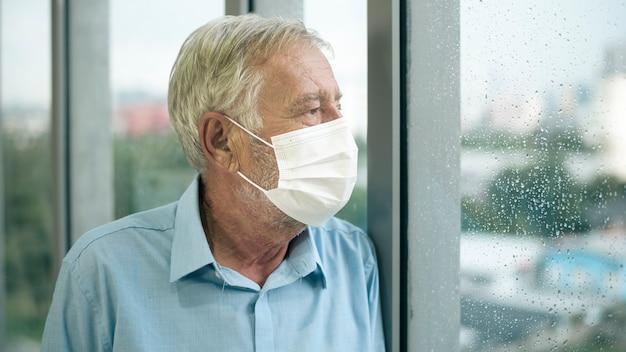 Homem caucasiano idoso está usando máscara médica, olhando para fora de sua casa