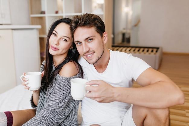 Homem caucasiano inspirado tomando café com a namorada na manhã de domingo