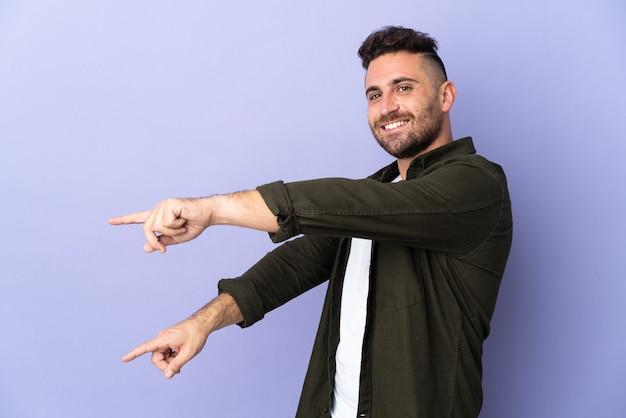 Homem caucasiano isolado em fundo roxo apontando o dedo para o lado e apresentando um produto