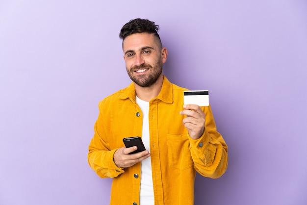 Homem caucasiano isolado em roxo comprando com o celular com um cartão de crédito