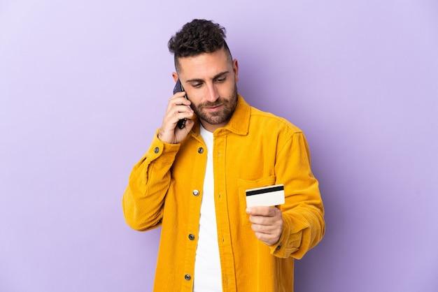 Homem caucasiano isolado em um fundo roxo, comprando com o celular com um cartão de crédito