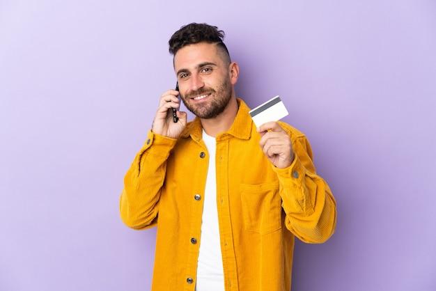 Homem caucasiano isolado em um fundo roxo, conversando com o celular e segurando um cartão de crédito
