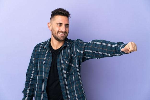 Homem caucasiano isolado em um fundo roxo fazendo um gesto de polegar para cima