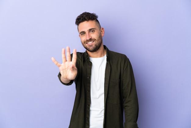 Homem caucasiano isolado em um fundo roxo feliz e contando quatro com os dedos