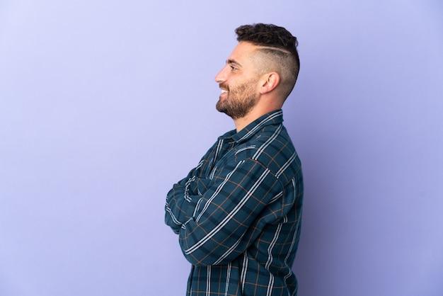 Homem caucasiano isolado em um fundo roxo na posição lateral