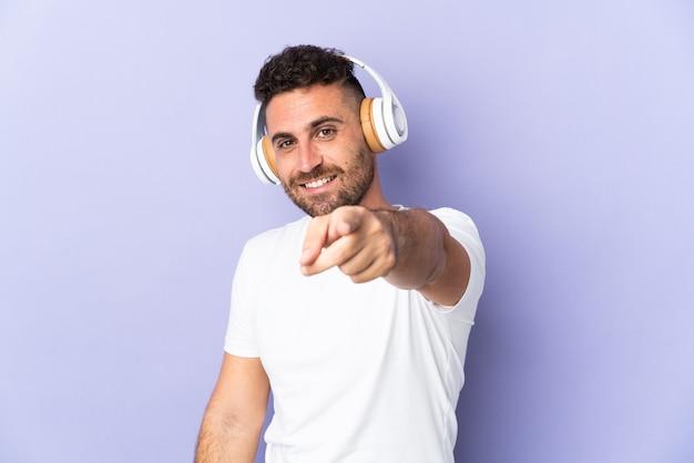Homem caucasiano isolado em um fundo roxo ouvindo música e apontando para a frente