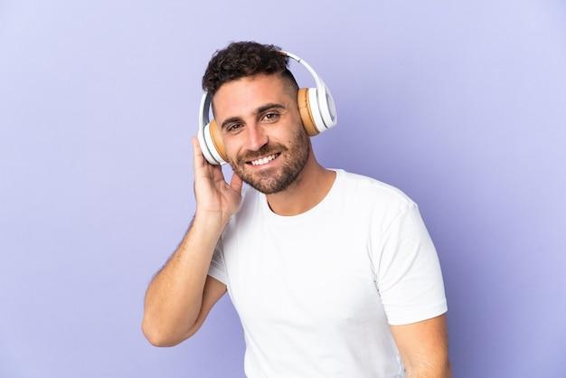 Homem caucasiano isolado em um fundo roxo ouvindo música
