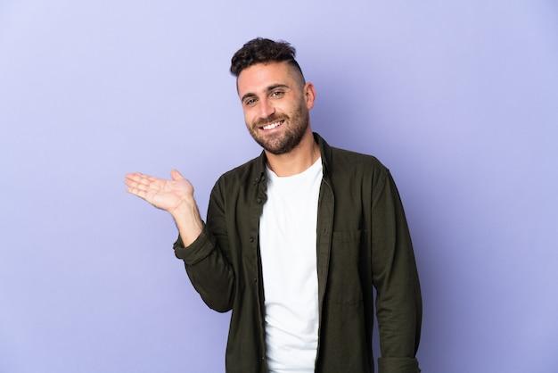 Homem caucasiano isolado em um fundo roxo segurando copyspace imaginário na palma da mão para inserir um anúncio