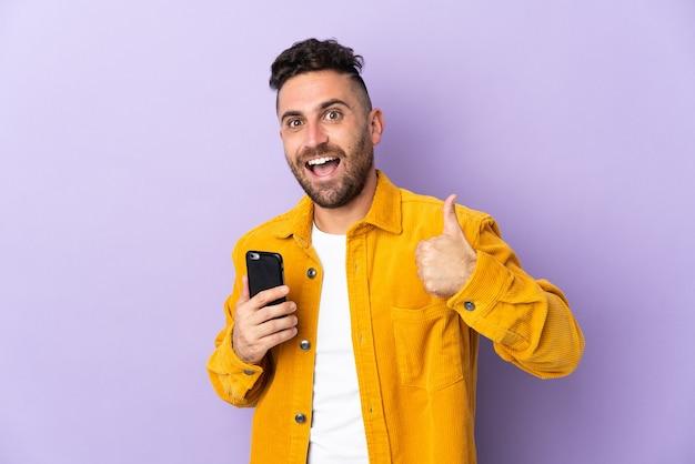 Homem caucasiano isolado em um fundo roxo usando um telefone celular enquanto faz o polegar para cima