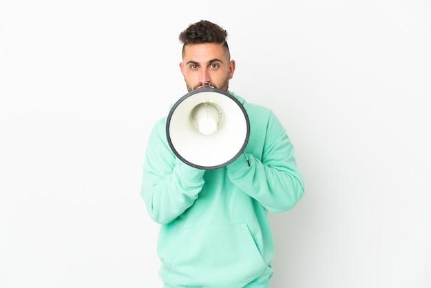 Homem caucasiano isolado na parede branca gritando em um megafone para anunciar algo