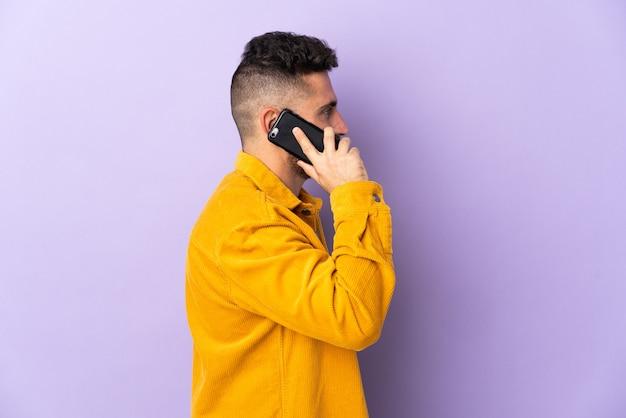 Homem caucasiano isolado na parede roxa, conversando com alguém com o celular