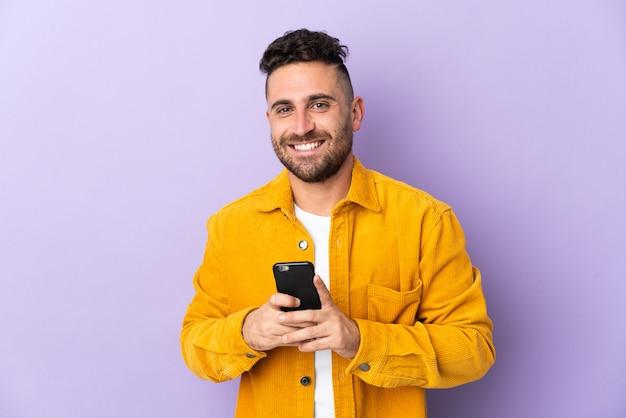 Homem caucasiano isolado na parede roxa, olhando para a câmera e sorrindo enquanto usa o celular