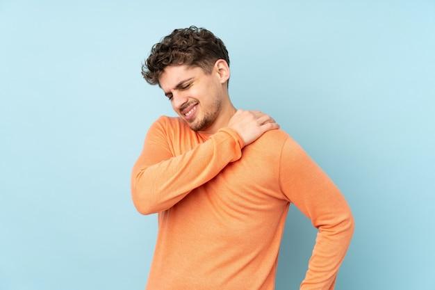 Homem caucasiano isolado no azul, sofrendo de dor no ombro por ter feito um esforço