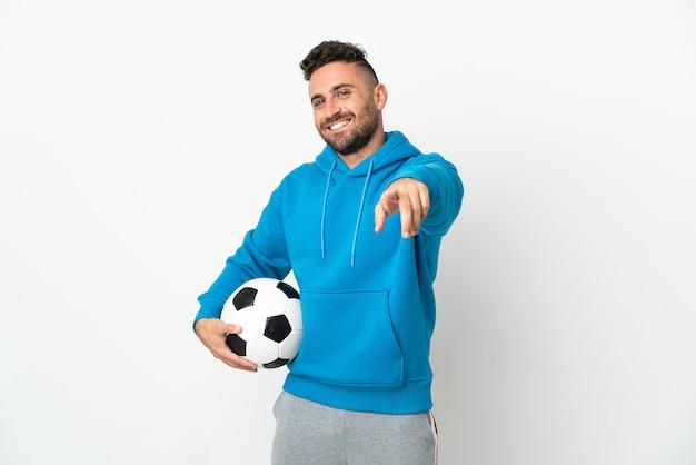 Homem caucasiano isolado no fundo branco com bola de futebol e apontando para a frente