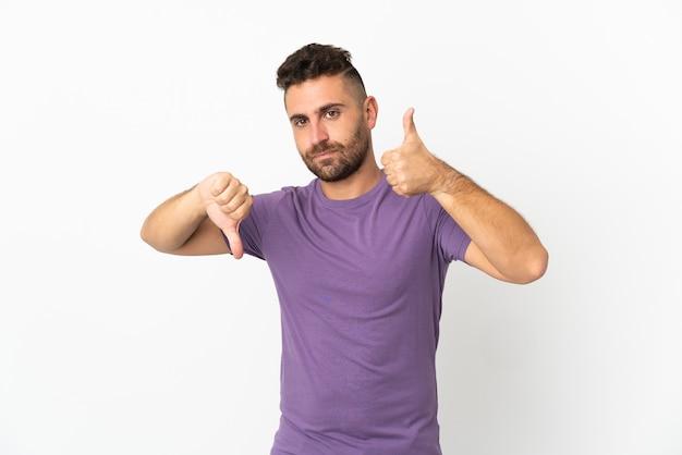 Homem caucasiano isolado no fundo branco, fazendo sinais de bom-ruim. indeciso entre sim ou não