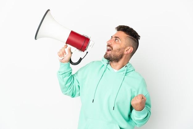 Homem caucasiano isolado no fundo branco gritando em um megafone para anunciar algo em posição lateral