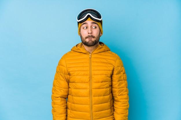 Homem caucasiano jovem esquiador isolado confuso, sente-se duvidoso e inseguro.