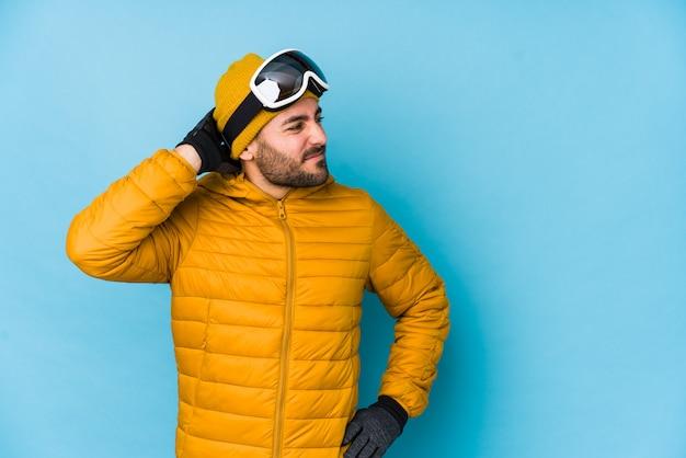 Homem caucasiano jovem esquiador isolado tocando a parte de trás da cabeça, pensando e fazendo uma escolha.
