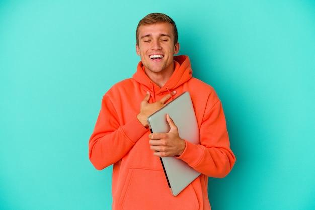 Homem caucasiano jovem estudante segurando um laptop isolado no azul ri em voz alta, mantendo a mão no peito.