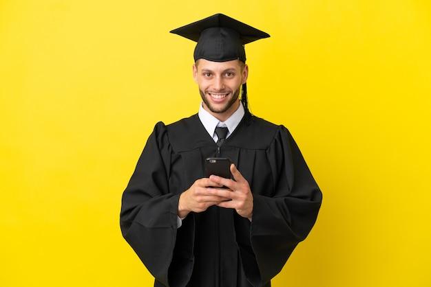 Homem caucasiano, jovem, formado em universidade, isolado em um fundo amarelo, enviando uma mensagem com o celular.