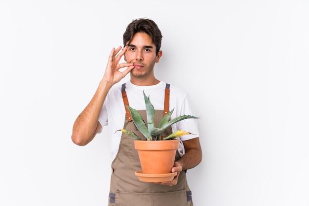 Homem caucasiano jovem jardineiro segurando uma planta isolada com os dedos nos lábios, mantendo um segredo.