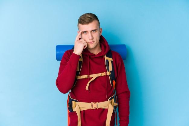 Homem caucasiano jovem viajante apontando o templo com o dedo, pensando, focado em uma tarefa.