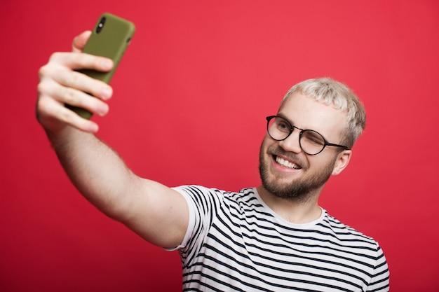 Homem caucasiano loiro com óculos fazendo uma selfie em uma parede vermelha