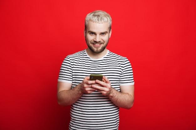 Homem caucasiano loiro conversando com seus amigos em um fundo vermelho enquanto olha para a câmera