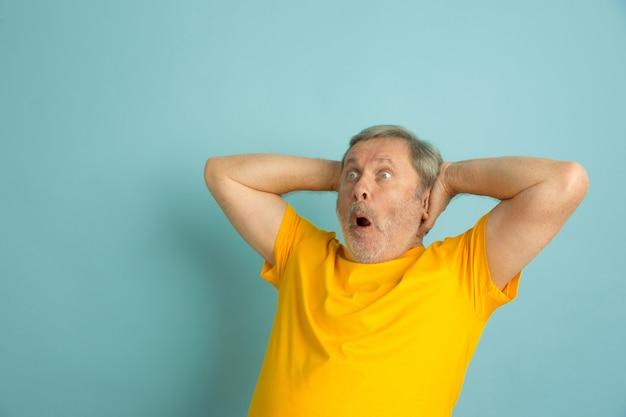 Homem caucasiano, louco chocado, espantado, isolado no azul