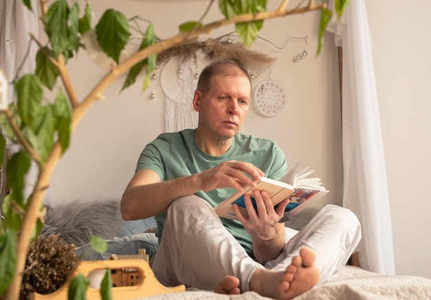 Homem caucasiano maduro lendo livro no interior moderno e elegante e aconchegante com a planta.