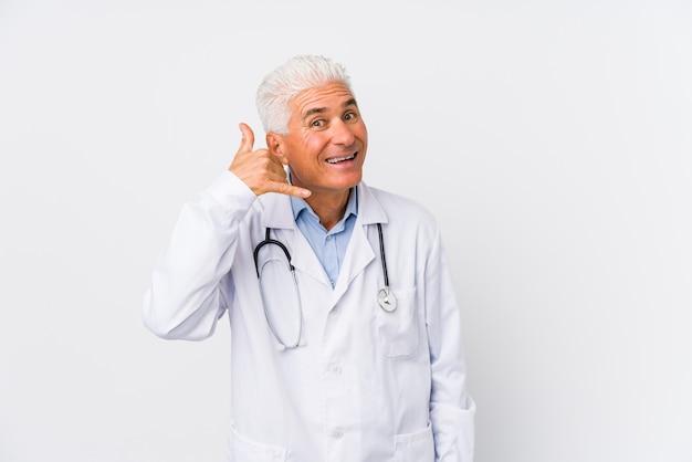 Homem caucasiano maduro médico mostrando um gesto de chamada de telefone móvel com os dedos.