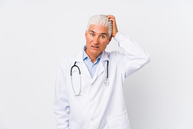 Homem caucasiano médico maduro estar chocado, ela se lembrou de uma reunião importante.