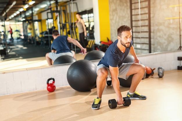 Homem caucasiano musculoso fazendo exercícios com halteres. no fundo, seu reflexo no espelho.