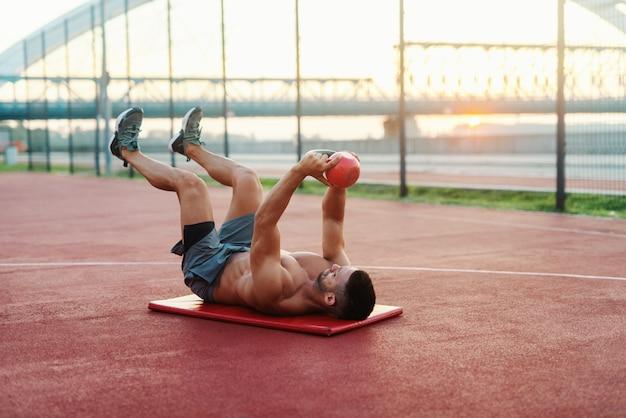 Homem caucasiano musculoso sem camisa com expressão facial séria, fazendo exercícios com kettlebell enquanto estava deitado no tapete na quadra pela manhã.
