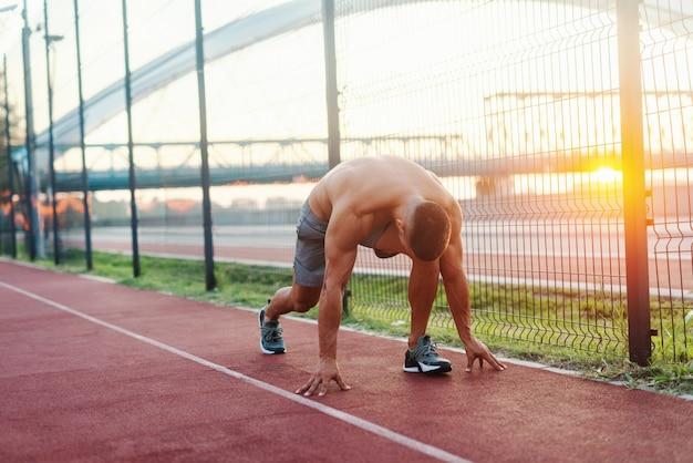 Homem caucasiano musculoso sem camisa de yong se preparando para correr na pista de corrida pela manhã.
