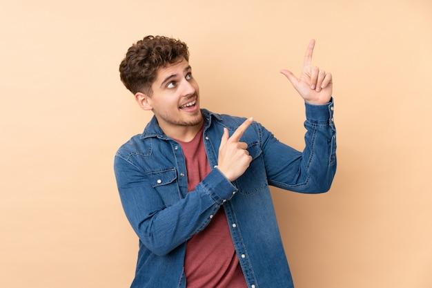 Homem caucasiano na parede bege, apontando com o dedo indicador uma ótima idéia