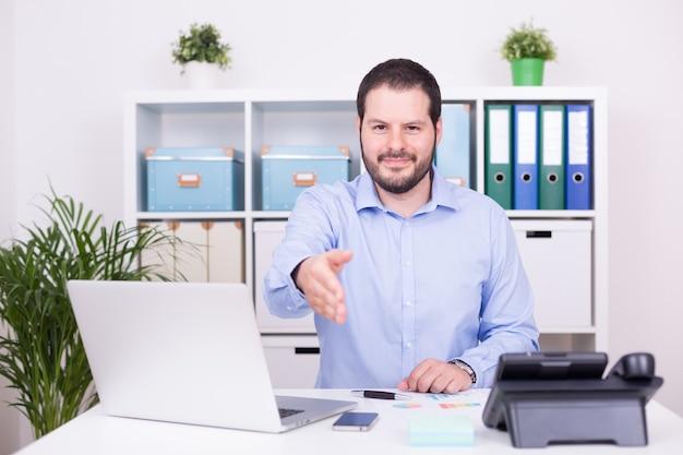 Homem caucasiano no escritório oferece cooperação com um aperto de mão