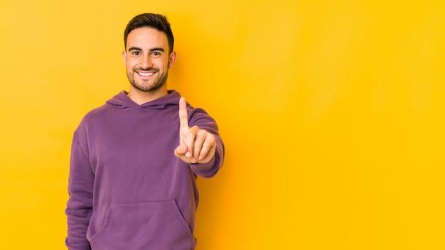 Homem caucasiano novo isolado no amarelo que mostra o número um com dedo.