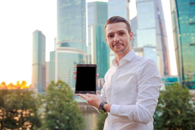 Homem caucasiano novo que guarda o smartphone para o trabalho do negócio.