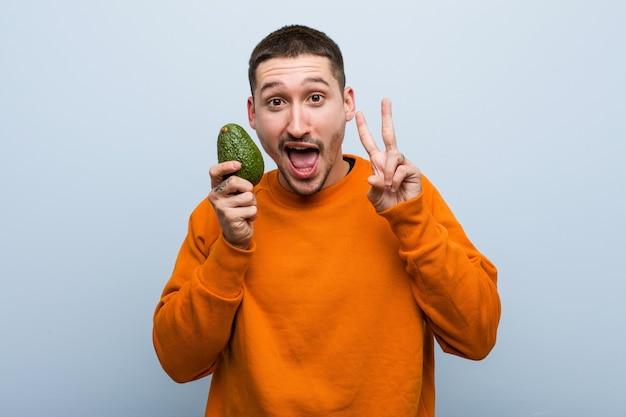 Homem caucasiano novo que guarda um abacate que mostra o sinal da vitória e que sorri amplamente.