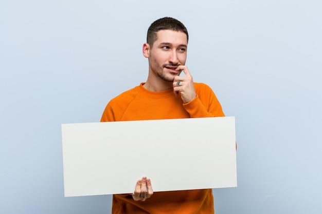 Homem caucasiano novo que guarda um pensamento relaxado cartaz sobre algo que olha um espaço da cópia.