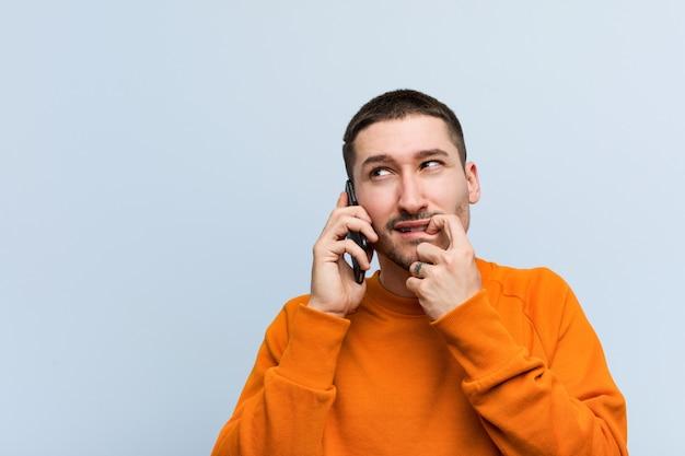 Homem caucasiano novo que guarda um pensamento relaxado do telefone sobre algo que olha um espaço da cópia.