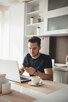 Homem caucasiano ocupado conversando no celular em casa enquanto trabalha no laptop e bebe um café