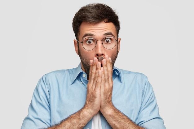 Homem caucasiano perplexo cobre a boca com as duas mãos, tem expressão perplexa de medo, não acredita em fracasso, olha fixamente através de óculos com olhos esbugalhados, vestido com uma camisa elegante, fica em um ambiente fechado.