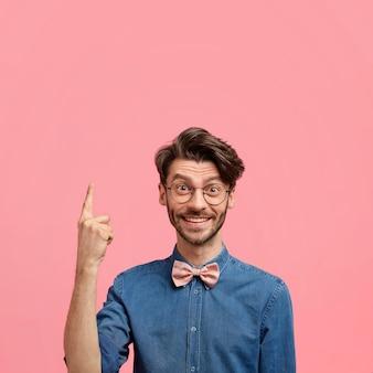 Homem caucasiano positivo com penteado moderno, cerdas escuras, feliz em notar algo acima, aponta com o dedo indicador