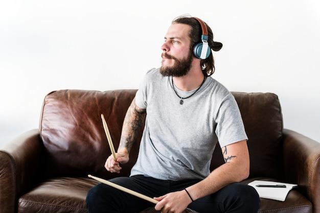 Homem caucasiano praticando tambor sozinho
