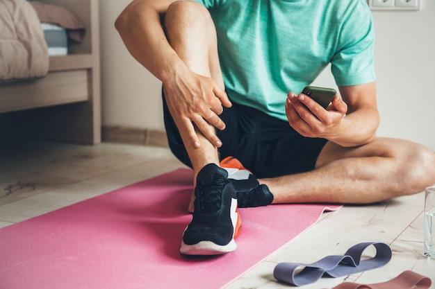 Homem caucasiano que faz exercícios em casa está descansando depois de fazer exercícios matinais enquanto olha para o telefone