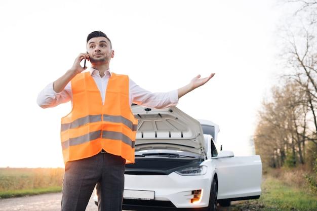 Homem caucasiano quebrou carro elétrico na estrada