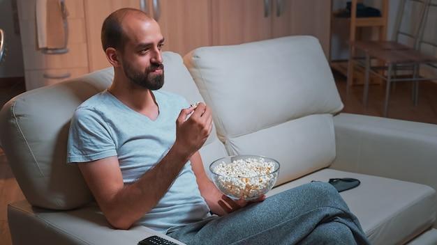 Homem caucasiano relaxando no sofá com a tigela de pipoca nas mãos enquanto assiste uma série de filmes na televisão. homem cansado de pijama assistindo a programas de entretenimento tarde da noite na cozinha